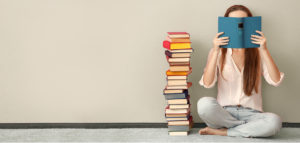 Gerry marsh web header - Woman sitting on floor with a pile of books - hiding face behind open book